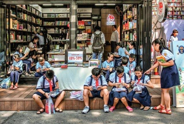 Các em thiếu nhi hăng say bên những cuốn sách truyện trên con đường sách này