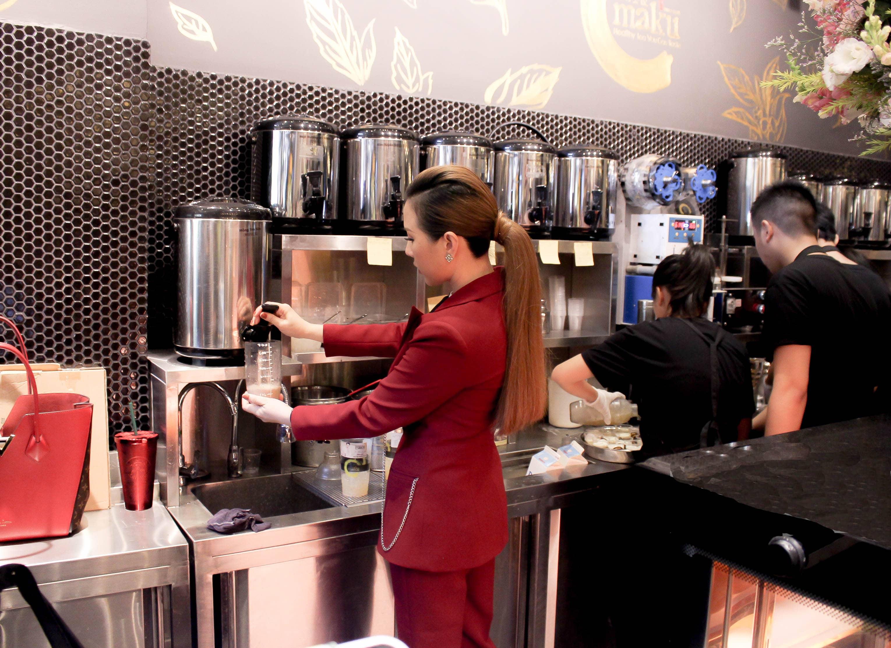 Hình ảnh hoa hậu Thu Hoài pha đồ uống cho khách