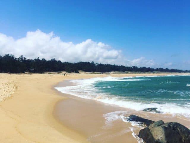 Bãi biển trải dài hình cong lưỡi liềm ôm trọn bờ cát mịn vàng quyến rũ du khách khi đặt chân đến đây (Ảnh sưu tầm)