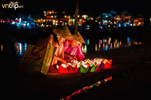 Bạn sẽ dễ dàng bắt gặp những cô gái bán đèn hoa đăng cạnh chùa Cầu (Ảnh: Sưu tầm)