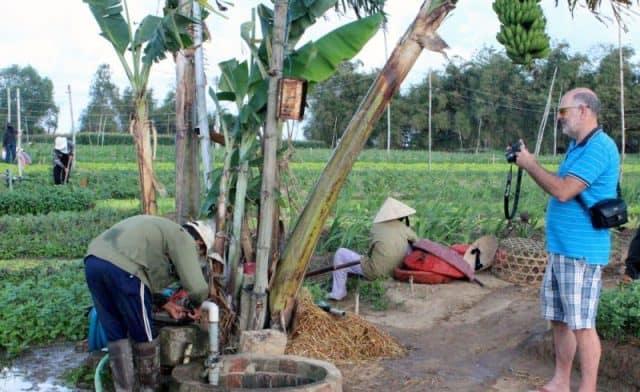 Du khách nước ngoài chụp lại hình ảnh người nông dân chuẩn bị máy bơm nước tưới rau (Ảnh ST)