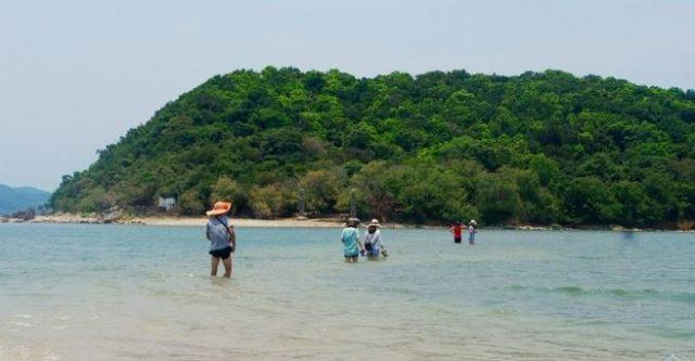 Khách du lịch băng qua con đường dưới mực nước biển để lên đảo khám phá (Ảnh ST)