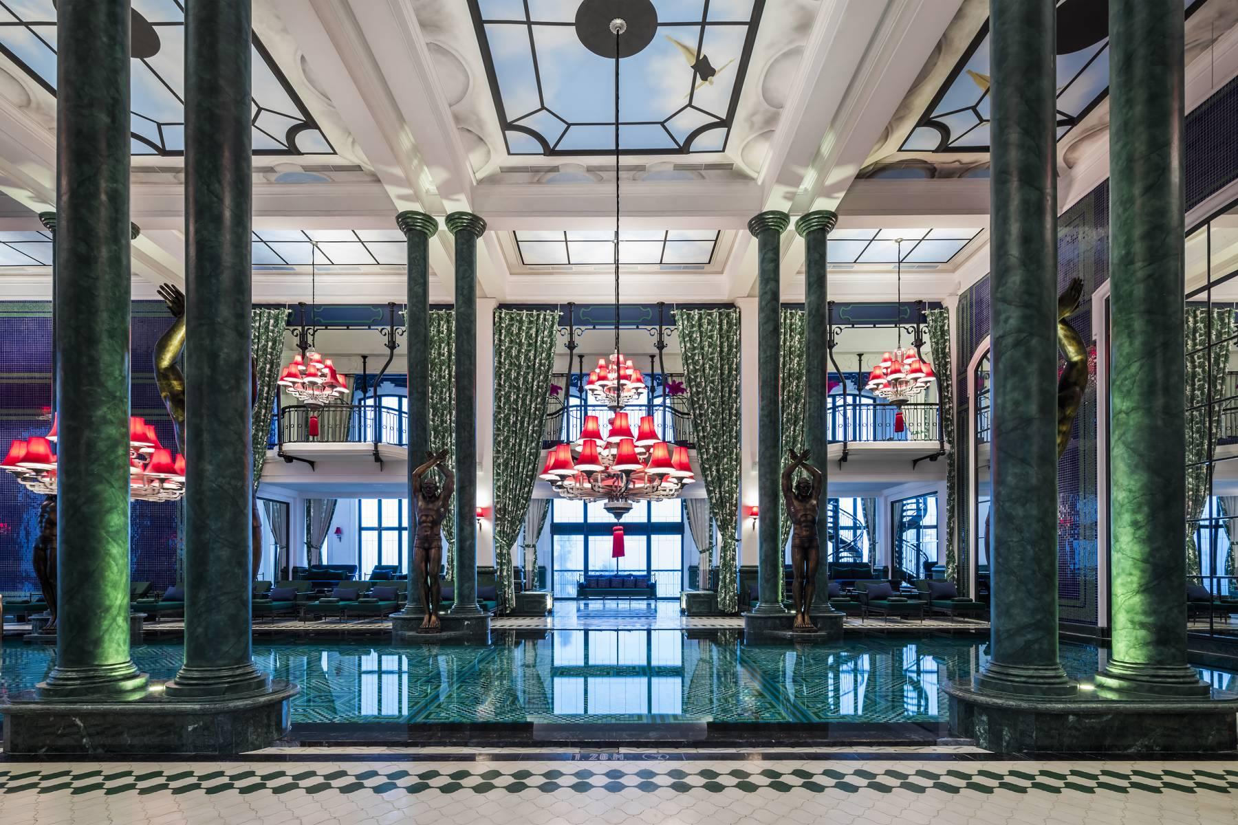 Không gian bể bơi lộng lẫy bởi những cột đá cẩm thạch xanh ngọc lục bảo, tượng đồng và đèn chùm rực rỡ