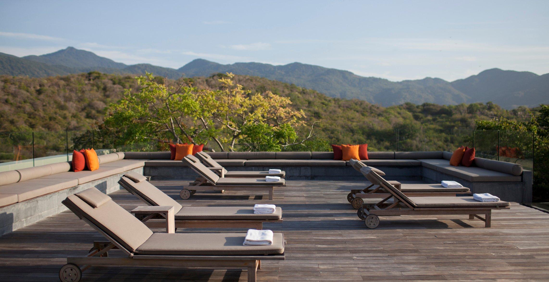 Một bể bơi riêng cùng với ghế nằm phơi nắng, thềm gỗ ngoài trời
