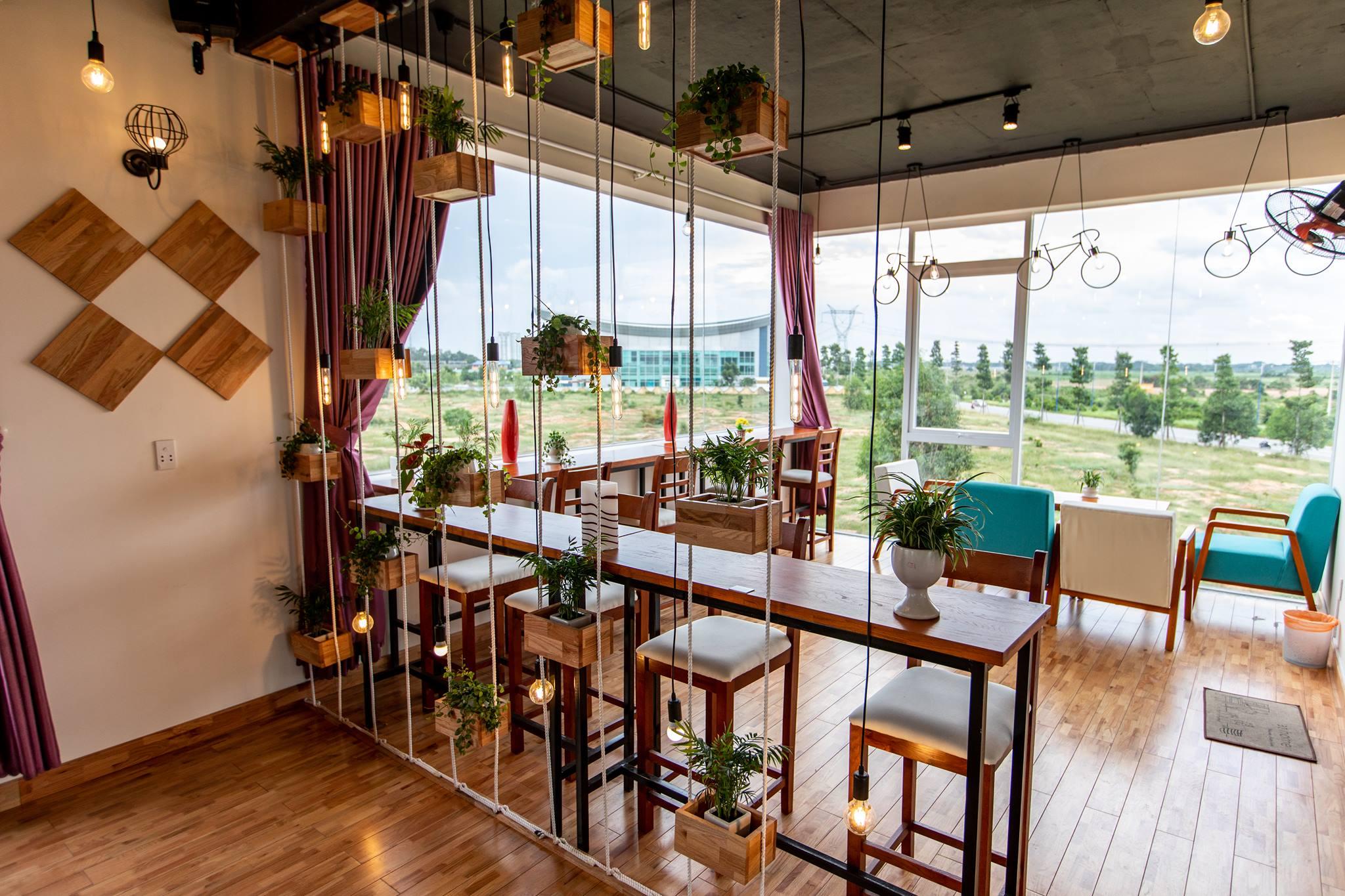 Hoàng Phúc Cafe được bố trí gần gũi với thiên nhiên, với những bộ ghế sofa màu xanh tựa màu lá cây, những chiếc bàn và ghế gỗ màu sắc nhẹ nhàng, tựa màu cát. Hình: Hoàng Phúc Cafe