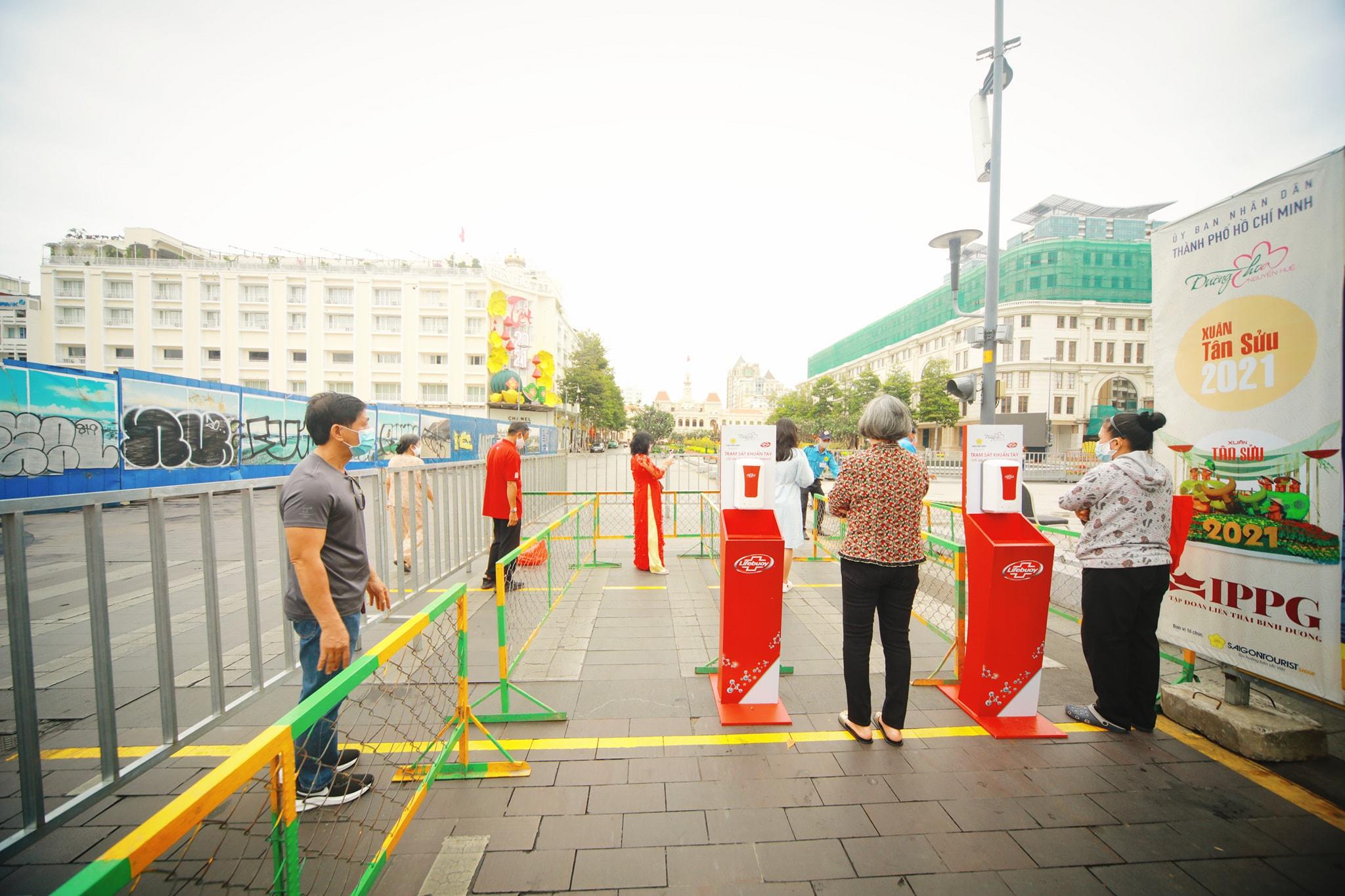 Những du khách đầu tiên đến phố đi bộ Nguyễn Huệ từ sớm đợi check-in qua cổng an ninh để đảm bảo an toàn mùa dịch - Nguồn ảnh: Huy NguyenAn